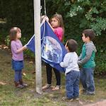 Children raising earth flag